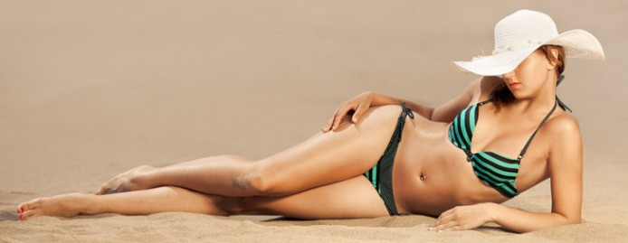 Bright photo of a beautiful model relaxing on a beach. Room for