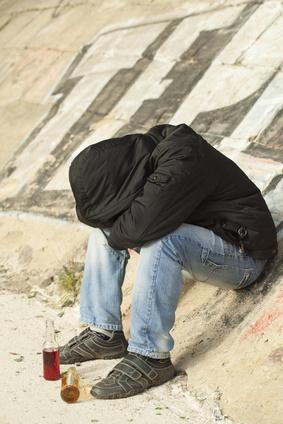 Boy sleeping under a bridge with two drink bottles near