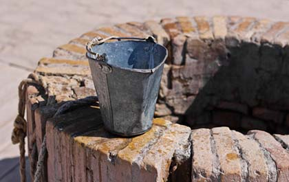 A water well with an old bucket